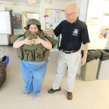 Sheila H. tries on protective clothing with Ken Doucette, Director of Community Affairs at the Middlesex Sheriff's Office.