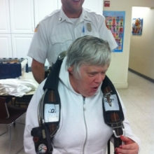 Dianne April tries on firefighting gear during a Watch City Self Advocates meeting. Members of the Waltham Fire Department spoke about fire safety.