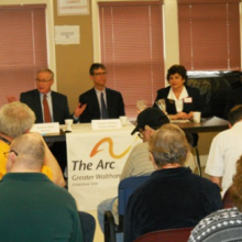 State Senator Mike Barrett (left) makes a point at the Legislative Town Meeting held January 31 at Woodland Road. Also pictured (l to r) are State Senator William Brownsberger, Roz Rubin and Kevin Larrivee, Legislative Director for Senator Barrett.