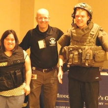 Ken Doucette, Director of Community Affairs, Middlesex Sheriff's Office, gets assistance from Sheila Hernandez and Danny Powers to model protective gear during his keynote presentation.