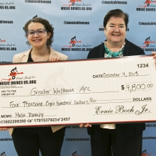 Leah Igdalsky, Grantwriter/ Development Associate, and Joanne Raymond, Director of Marketing and Development, receive a grant check for music therapy at the Music Drives Us office.