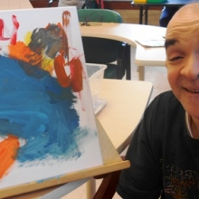 Tommy proudly displays art work her created with a Bentley student volunteer in March, 2016.